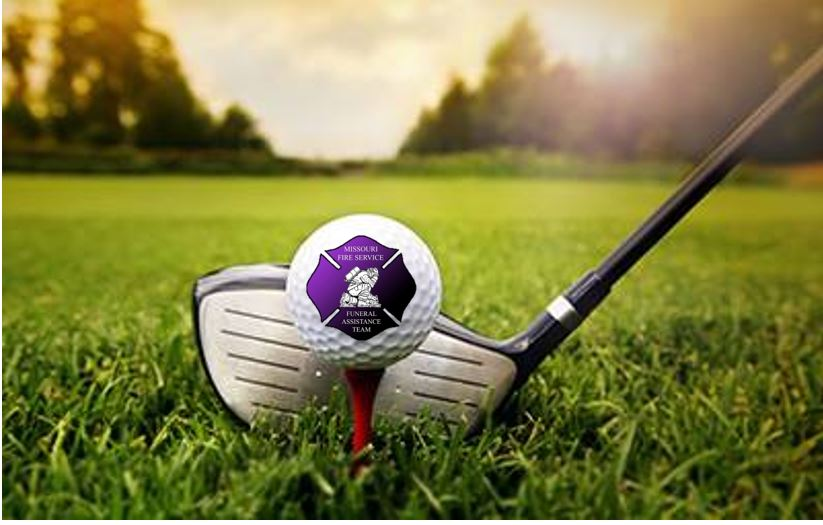 close up of golf club on grass behind a set golf ball with a purple Missouri Fire Service logo